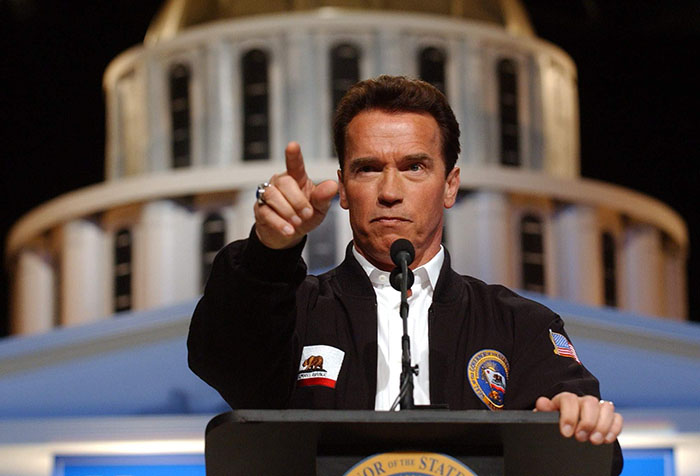Gov. Arnold Schwarzenegger points to a reporter while taking questions during a news conference at Cal Expo in Sacramento, Calif., Wednesday, Feb. 23, 2005. Standing in front of a mock-up of the state Capitol, Schwarzenegger called on lawmakers to approve a constitutional amendment that automatically cuts state spending across the board if spending execeeds state revenues. (AP Photo/Rich Pedroncelli)